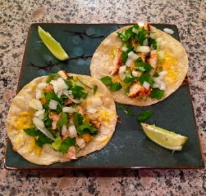 Chicken tacos made with: corn tortillas, low fat mexican cheese blend, cilantro, onions, organic chicken (seasoned with garlic powder, onion powder, pepper, chille powder, and cayenne pepper), homemade quacemole, homemade chipotle sauce